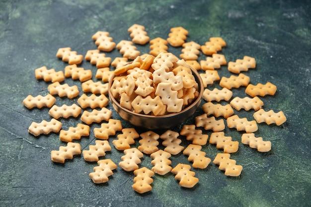 Vista frontale piccoli cracker all'interno del piatto su sfondo grigio scuro colore croccante snack cips sale pane fette biscottate cibo pepe