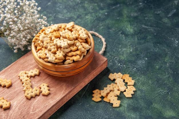 Vista frontale piccoli cracker all'interno del piatto su sfondo grigio scuro fette biscottate croccanti snack pane sale cibo cips colore