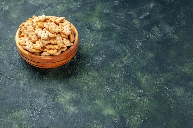 暗い背景のプレート内の正面図小さなクラッカークリスプスナック塩パンラスク食品cips色