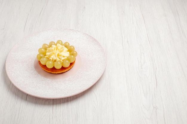 正面図白い背景の上のブドウと小さなクリームケーキパイフルーツケーキデザートビスケットクッキー