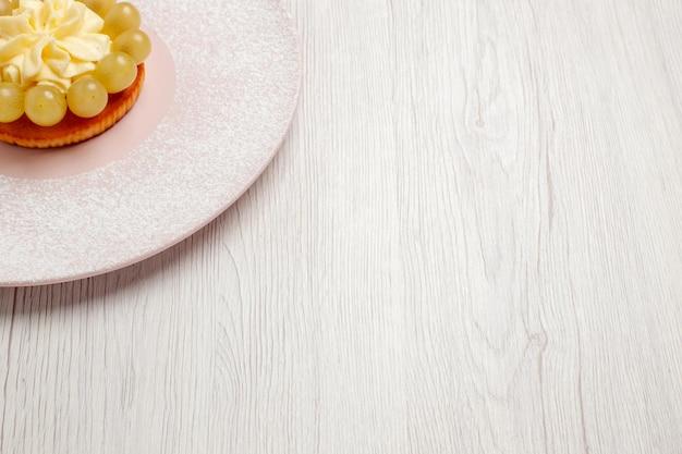 正面図白い床にブドウと小さなクリームケーキパイフルーツケーキデザートビスケットクッキー