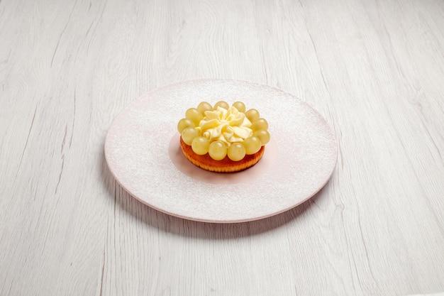 Vista frontale piccola torta alla crema con uva su sfondo bianco torta alla frutta dolce biscotto biscotto
