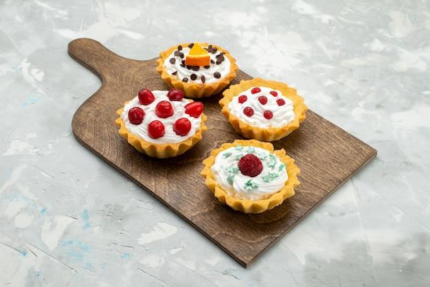 Вид спереди маленькие кремовые пирожные с фруктами на светло-сером столе, сахарная конфета