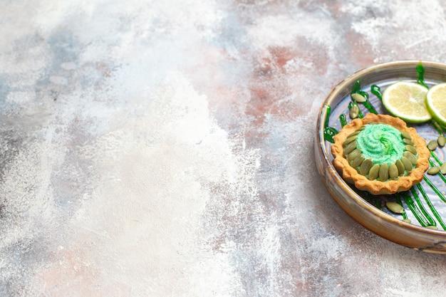 トレイの中に果物が入った正面図の小さなクリーミーなケーキ