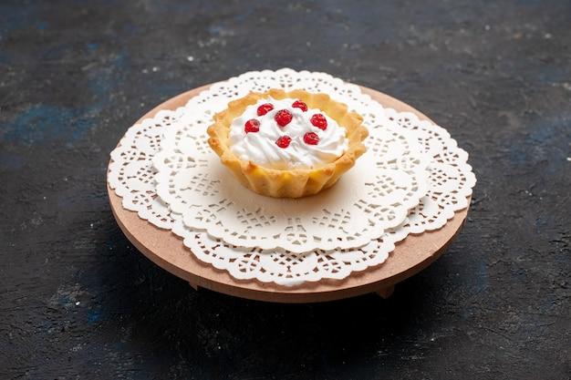 Vista frontale piccola torta cremosa con frutti rossi sulla crema dolce zucchero scuro scrivania