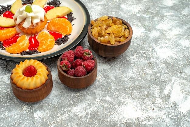 흰색 배경에 얇게 썬 사과와 감귤을 넣은 작은 크림 케이크, 달콤한 비스킷 케이크 파이 설탕