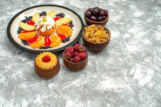 正面図白い背景の上のスライスしたリンゴとみかんの小さなクリーミーなケーキフルーツ甘いビスケット砂糖ケーキパイ