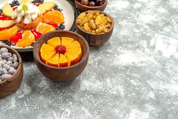 Vista frontale piccola torta cremosa con frutta a fette e uvetta su sfondo bianco torta dolce di frutta torta di zucchero biscotto
