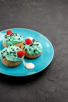 正面図小さなクリーミーなケーキダークデスクのプレート内のお茶のためのおいしいお菓子クリームケーキビスケットデザートティーカラー