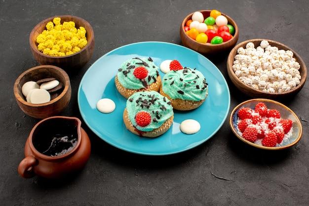 Vista frontale piccole torte cremose con caramelle su sfondo grigio scuro torta da dessert biscotto caramelle biscotto colore