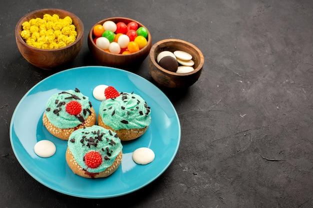 正面図暗い背景にキャンディーと小さなクリーミーなケーキデザートケーキビスケットカラーキャンディークリーム