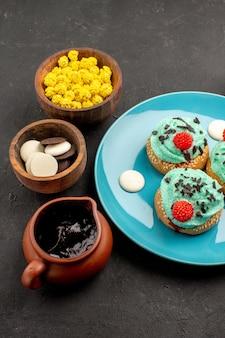 正面図ダークグレーの背景にキャンディーと小さなクリーミーなケーキデザートケーキビスケットキャンディークッキーの色