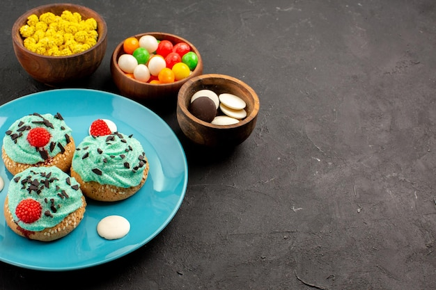 正面図ダークグレーの背景にキャンディーと小さなクリーミーなケーキデザートケーキビスケットカラーキャンディークリーム