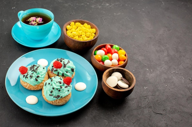 Vista frontale piccole torte cremose con una tazza di tè e caramelle su sfondo scuro torta alla crema di tè biscotto dessert color