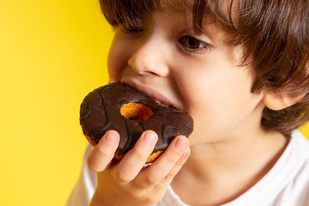 Un ragazzino sveglio di vista frontale che mangia le ciambelle