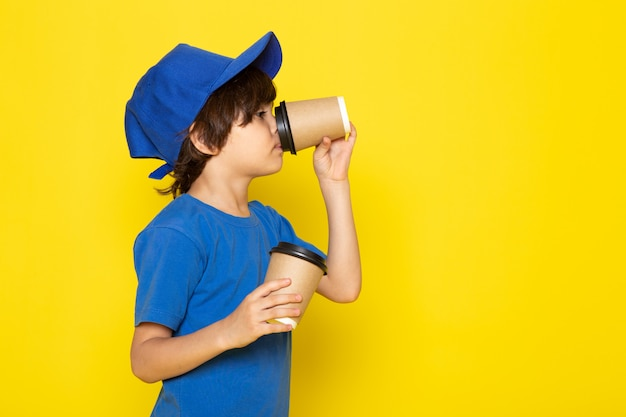 A front view little cute courier in blue t-shirt blue cap holding coffee cups