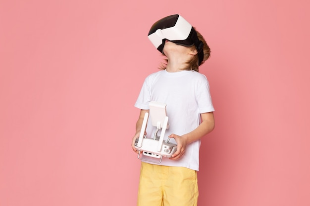 A front view little cute kid in white t-shirt playing vr in white t-shirt and yellow jeans on the pink floor