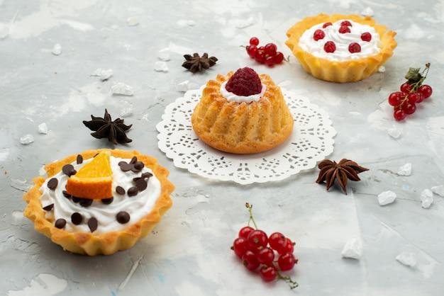 Вид спереди маленькие пирожные со сливками и разными фруктами, изолированные на светлой поверхности, сахар, сладкий чай