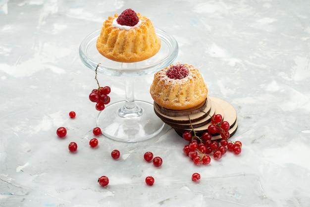 Вид спереди маленькие пирожные со сливками и красной клюквой на светлом столе сладкие сахарные фрукты