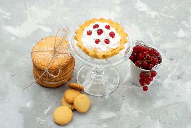 正面の明るい表面の甘い砂糖フルーツのクリームクッキーと赤いクランベリーと小さなdケーキ