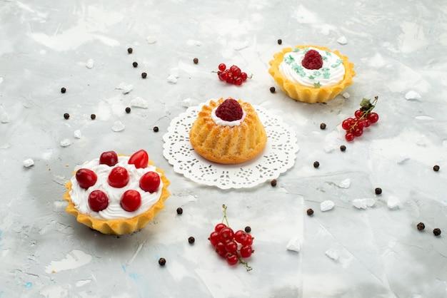 Vista frontale piccole torte d con crema e diversi frutti isolati sulla superficie leggera dolce