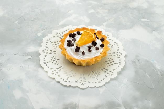 正面の軽い表面のケーキの甘い生地砂糖にクリームとドライフルーツと少しおいしいケーキ
