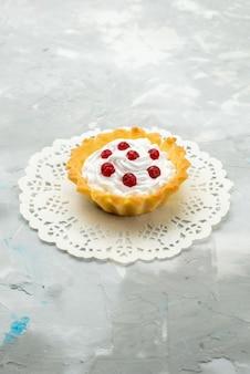 Вид спереди маленький вкусный торт со сливками и красной клюквой, изолированные на светлой поверхности