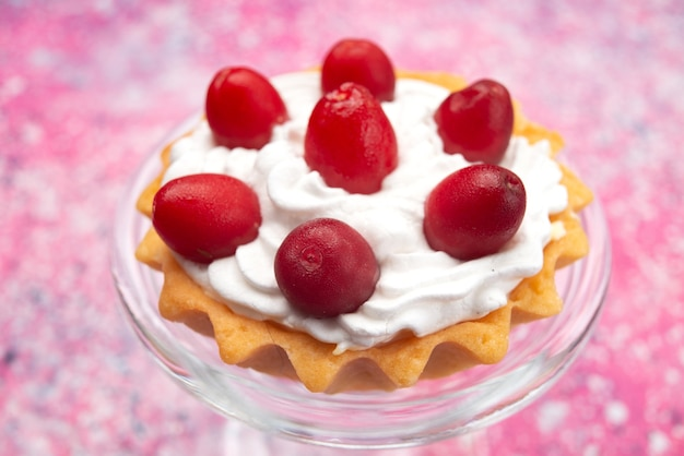 明るい表面砂糖甘いにクリームと赤い果物と少しおいしいケーキの正面図