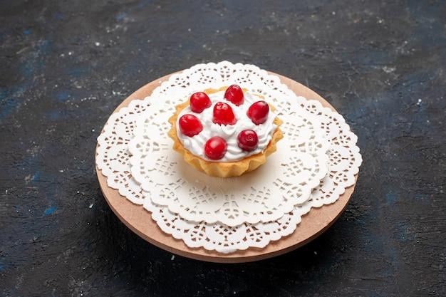 Маленький вкусный торт со сливками и красными фруктами на темном столе, вид спереди
