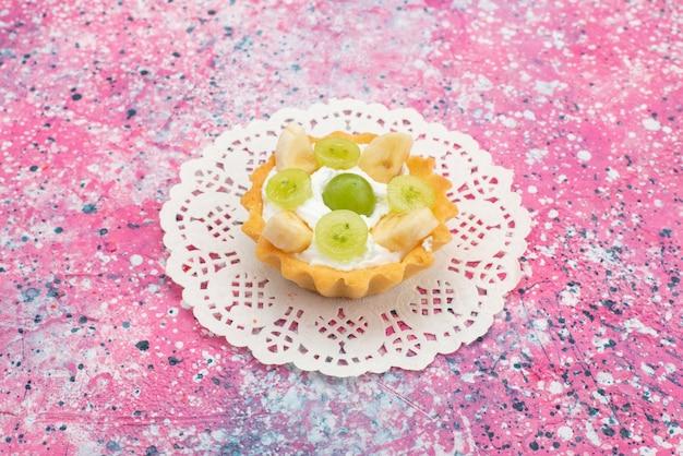 正面の色の表面に甘いクリームとスライスされたフルーツの小さなおいしいケーキ