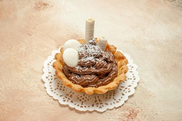 明るい背景にクリーム色の小さなおいしいケーキを正面から見る