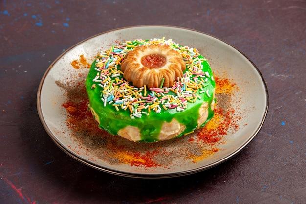 Vista frontale piccola deliziosa torta con crema verde sulla parete scura biscotti biscotti torta di zucchero dolce torta