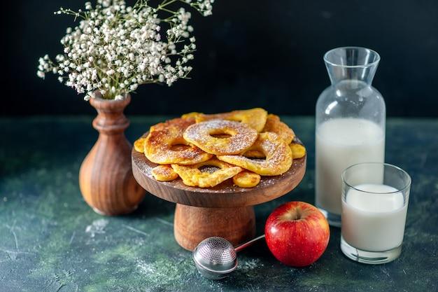 전면 보기 어두운 과일 파이 페이스트리 케이크 핫케이크 색상 베이킹에 우유와 파인애플 링 모양의 작은 맛있는 케이크