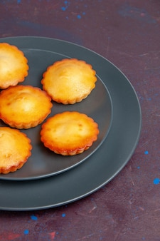 Front view little delicious cakes inside plate on dark background pie biscuit cake sweet tea cookies sugar
