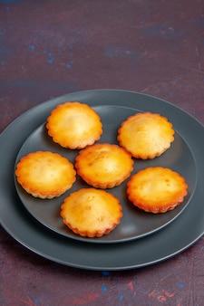 어두운 배경 파이 비스킷 케이크 달콤한 차 쿠키 설탕에 접시 안에 있는 작은 맛있는 케이크 전면 보기