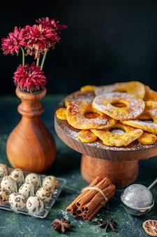 Vista frontale piccole deliziose torte a forma di anello di ananas con latte su una torta al forno scura torta di biscotti torta di frutta pasticceria