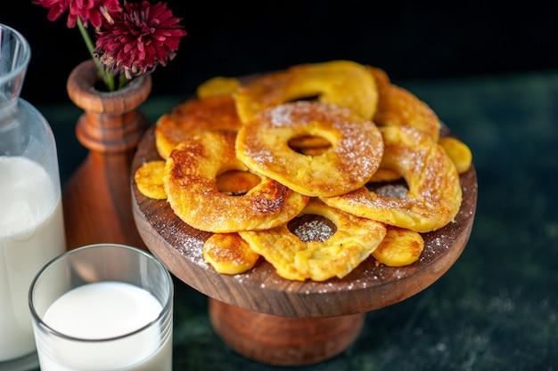 Vista frontale deliziose torte a forma di anello di ananas con latte sulla superficie scura