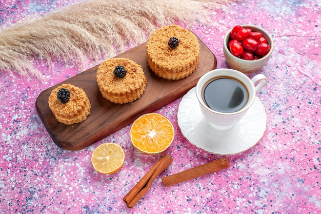 Front view of little delicious cakes with cinnamon and cup of tea on light pink surface