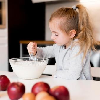 Vista frontale della bambina che cucina a casa