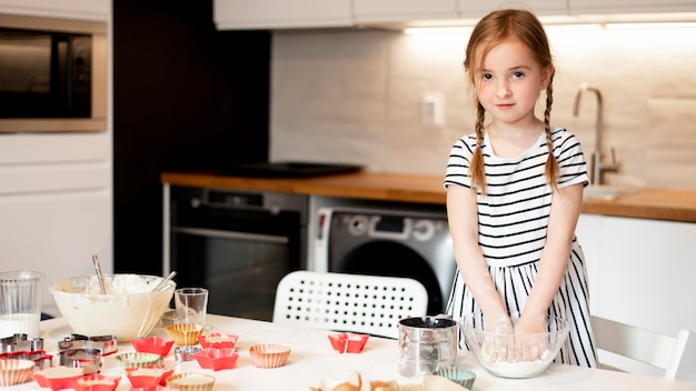 Front view of little girl cooking at home
