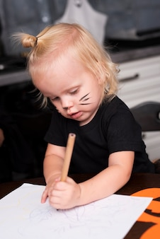 Front view of little girl drawing in the kitchen