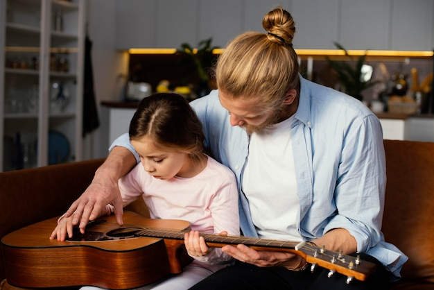 Front view of little girl and father playing guitar together