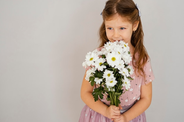 Front view of little girl holding bouquet of spring flowers with copy space