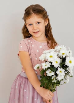 Front view of little girl holding bouquet of spring flowers