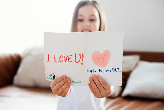 Front view of little girl holding a father's day card as a surprise for her dad