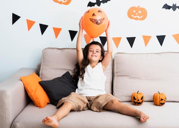 Front view little girl holding a halloween balloon