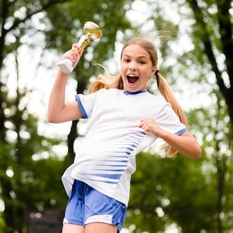 Вид спереди маленькая девочка прыгает после победы в футбольном матче