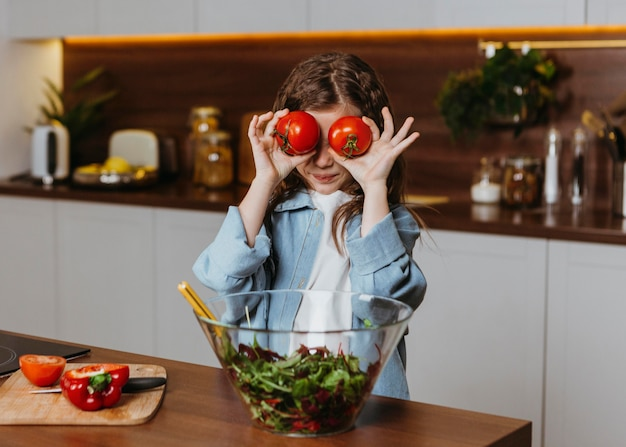 Front view of little girl in the kitchen with tomatoes