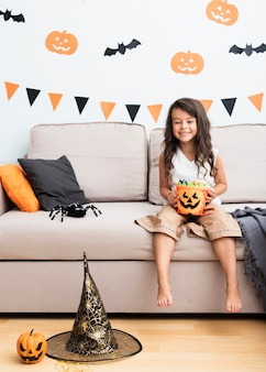 Front view little girl sitting on couch on halloween
