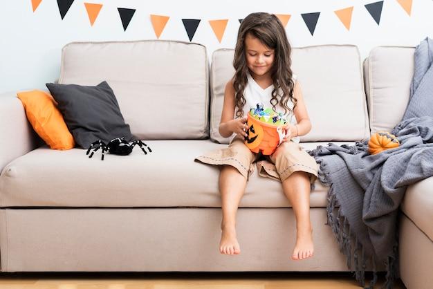 Вид спереди маленькая девочка, сидя на диване на хэллоуин Бесплатные Фотографии